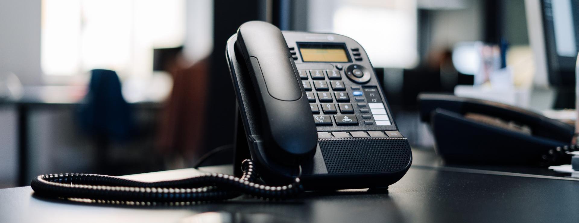 Black multiline phone on desk near window