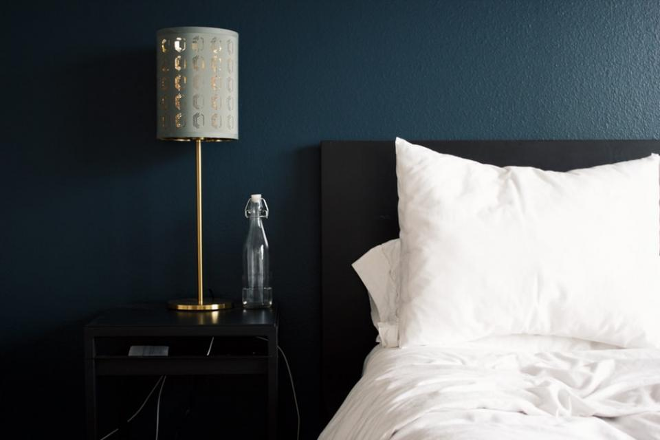 white bed and pillows with nightstand and lamp
